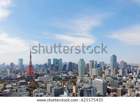 Beautiful city skyline of Downtown Tokyo, with the famous landmark Tokyo Tower standing tall among crowded skyscrapers under blue sunny sky in Tokyo, Japan. Aerial view of busy Tokyo City