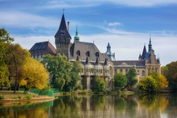Beautiful cityscape of Vajdahunyad castle in Varosliget park, Budapest with reflection on the lake and blue sky background
