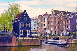 Beautiful cityscape with buildings and boat on the canal in Amsterdam, Netherlands