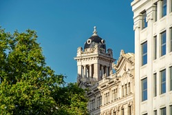 Beautiful classical building is seen through the green trees against the blue sky background on Catalonia Square (Placa de Catalunya) in Barcelona, Spain