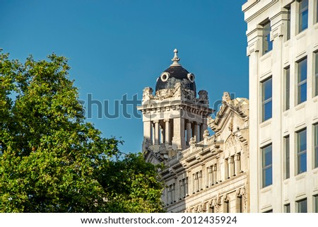 Beautiful classical building is seen through the green trees against the blue sky background on Catalonia Square (Placa de Catalunya) in Barcelona, Spain Foto stock ©