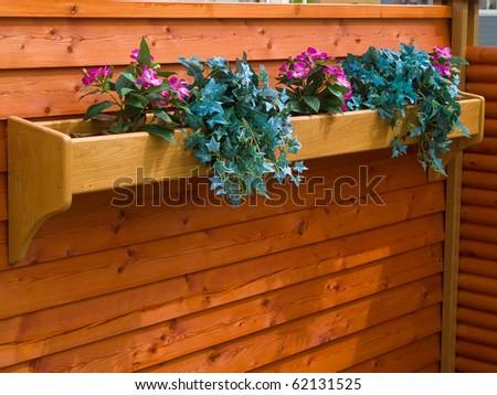 Beautiful classical design planter flowerpot on a garden wooden fence