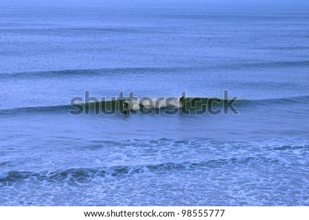 beautiful clean atlantic ocean with two surfers catching the waves on Irelands coast