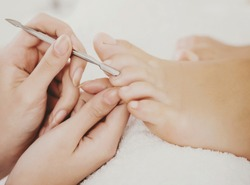 Beautiful Clean Female Fingers in Spa Composition. Pedicure Process in Beauty Salon. Cuticle Removal on Toes. Female Pedicure Closeup. Process of Professional Pedicures. Concept of Beauty and Health.