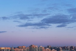 Beautiful clear, morning sky over the city at sunrise, natural background. Soft pink clouds.