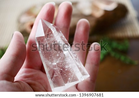 Beautiful Clear Quartz tower, and fresh pink rose flowers. Bright Quartz crystal, healing crystal being held in hand. Woman holding quartz tower, crisp colors in natural lighting. Vibrant meditation. #1396907681