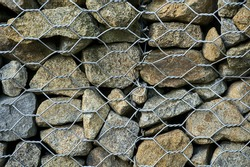 Beautiful close up high resolution view of gabion wall rocks and stones in metal wire box cage along M-50 motorway for slope and earth retention management  in Dublin, Ireland