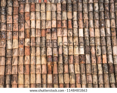 Beautiful close up photograph of old and weathered red clay tile roofing with rounded tiles overlapping one another in rows on a European home in Dubrovnik Croatia. #1148481863