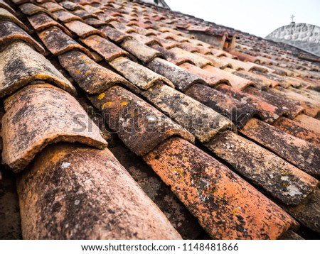 Beautiful close up photograph of old and weathered red clay tile roofing with rounded tiles overlapping one another in rows on a European home in Dubrovnik Croatia. #1148481866