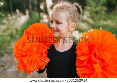 Beautiful close-up portrait of a smiling blonde girl, child cheerleader in a black suit with orange big pom-poms in her hands on nature in the forest at sunset. Sports training for cheerleading. ストックフォト ©