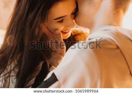 Beautiful close up portrait of an caucasian young couple embracing against light, while boy is kissing his girlfriend cheek which is smiling.