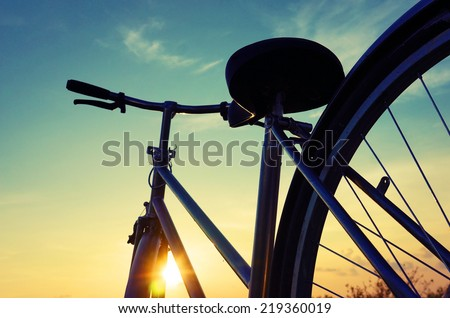 Beautiful close up scene of bicycle at sunset, sun on blue sky with vintage colors, silhouette of bike forward to sun, wonderful rural of Mekong Delta, Vietnam countryside