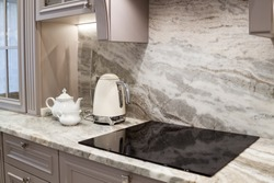 beautiful closeup of custom designed kitchen, with marble looking quartz countertop and backsplash. cream electric kettle with porcelain tea accessories on the marble countertop next to ceramic hob