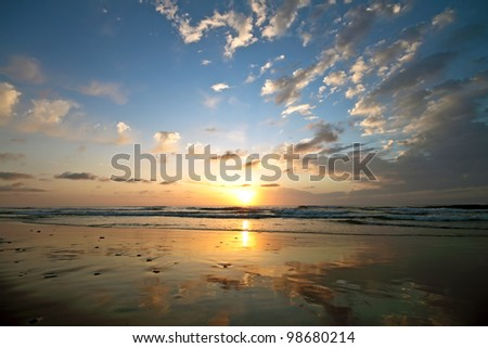 Beautiful cloudscape at the beach at sunset