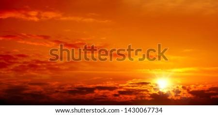 Beautiful cloudscape of orange colored sunset sky with shining sun #1430067734