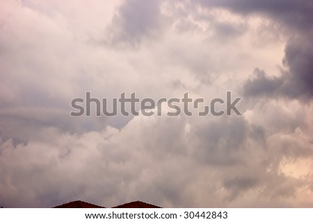 beautiful cloudscape of storm clouds gathering over roof tops with lots od space for copy could be used as a background