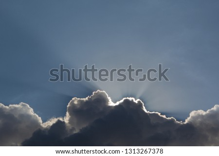 Beautiful cloudscape with large, building clouds and sunset behind shining sun rays and eventually breaking through cloud mass. #1313267378
