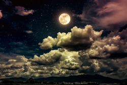 Beautiful cloudscape with many stars. Night sky with bright full moon and dark cloudy above mountain range among town. Serenity nature background. The moon taken with my own camera.