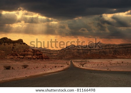 Beautiful cloudy evening sky over narrow road running towards mountains of Arava desert in Israel.
