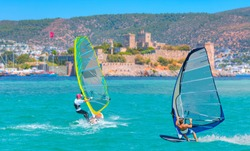 Beautiful cloudy sky with Windsurfer Surfing Wind On Waves - Saint Peter Castle (Bodrum castle) and marina in Bodrum, Turkey