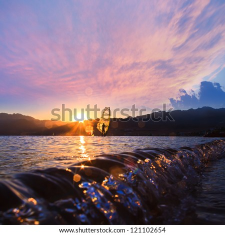 beautiful cloudy sunset on the beach with small glossy waves and windsurfers sails - stock photo