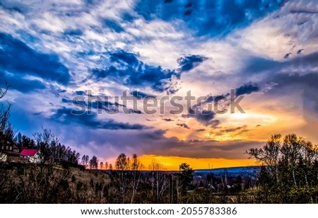 Beautiful cloudy sunset over the fields. Rural sunset landscape. Countryside at sunset. Sunset sky view