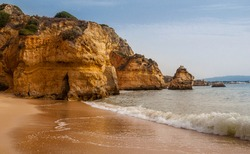Beautiful coast of Lagos in Portugal. The Algarve coast has almost two hundred kilometers of coastline and over a hundred sandy beaches. Rest on the beach surrounded by rocks. Beauty of nature.