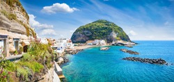Beautiful coast of village Sant'Angelo, giant green rock in blue sea near Ischia Island, Italy. Sunny day, blue sky with white clouds and azure sea.