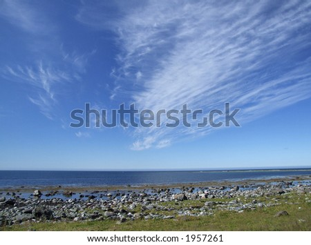 Beautiful coast view with picturesque white clouds. - stock photo