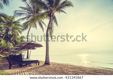 Beautiful coconut palm tree on the beach and sea with umbrella and chair on sunrise time - Vintage Filter #421345867