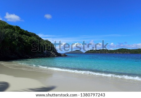 Beautiful Coki Beach in St. Thomas US Virgin Islands with blue water, clear skies, fluffy white clouds and green islands surrounding the beach #1380797243