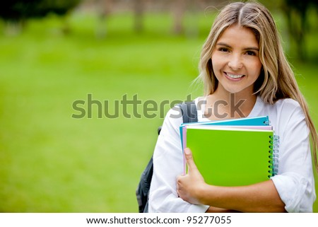 Beautiful college student holding notebooks and smiling