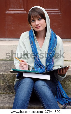 Beautiful college student wearing hooded sweater and colorful neck scarf while studying on campus.
