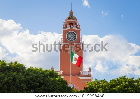 Beautiful colonial city of Merida. Red brick building tower with golden dome and clock in the City center of Merida. Mexican flag flutters on air. City Town hall of Yucatan in Mexico