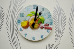 Beautiful color clock with painted dial and creative hands. Clock hanging on the wall. Interior decoration in any room in the house. On the mechanical clock painted fruit.