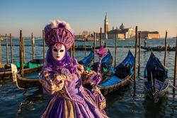 Beautiful colored carnival costume on the street in Venice. Carnival of Venice. Woman in purple dress near sea and gondola