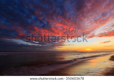 Beautiful colored clouds over the ocean at the beach at sunset #350603678