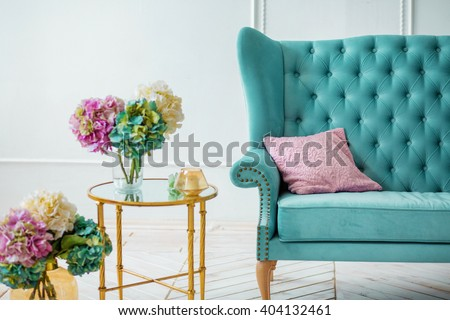 Beautiful colorful bouquet of hydrangeas is in a vase on a table with candles near the sofa with a pillow interior decor idea