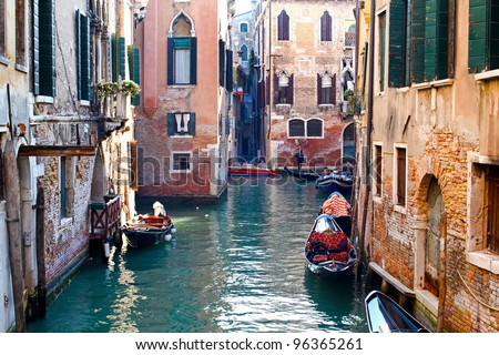 Beautiful colorful canal in Venice with parked gondolas near traditional architecture, Italy #96365261