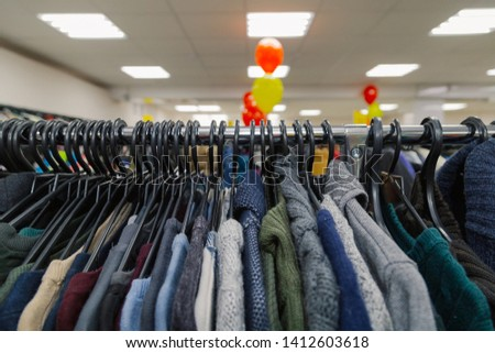 Beautiful colorful clothes in a store on hangers. #1412603618