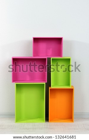 Beautiful colorful crates as shelves standing in room