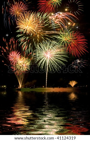 Beautiful colorful fireworks with night sky and lake reflections