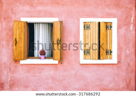 Beautiful colorful house facade on Burano island, north Italy. Red two windows with wooden shutters