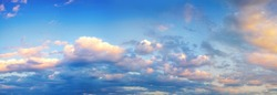 Beautiful colorful panorama of blue sky with white and pink scattered cumulus clouds during summer sunrise or sunset. Panoramic view.