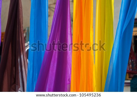 Beautiful colorful scarves hanging  in a fashion accessories shop