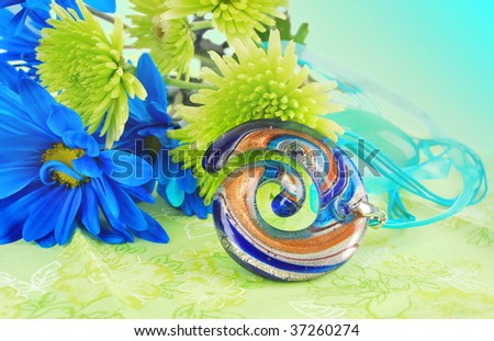 Beautiful colorful spiral glass pendant  with fantastic green  flowers are on the bright green napkin background.  (It's nice present idea).