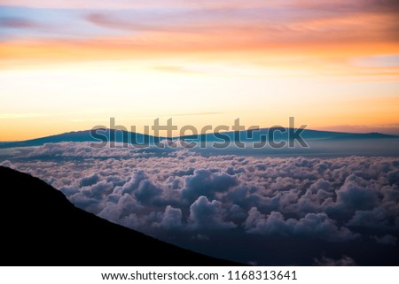 Beautiful Colorful Sunrise Sky at Dawn from the Top of Haleakala Volcano in Maui Hawaii Above the Clouds with Mountains in Background of Amazing Landscape in Island Paradise