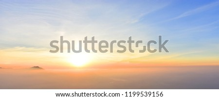 Beautiful colorful sunset at the edge of the Alps with some mountains sticking out of the haze (Bavaria, Germany). Copy space for multiple purposes.