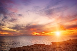 Beautiful colorful sunset at the sea with dramatic clouds and sun shining. Beauty world natural outdoors travel background
