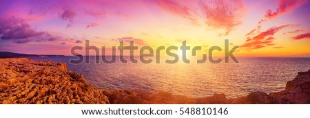 Beautiful colorful sunset at the sea with dramatic clouds and sun shining. Panoramic view. Beauty world natural outdoors travel background